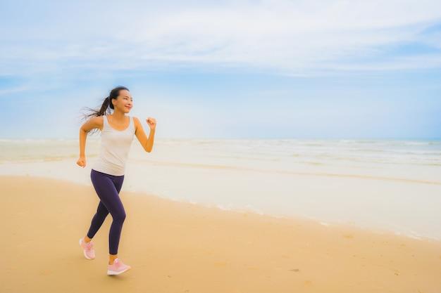 Asiatische frauenübung des schönen jungen sports des porträts durch laufen und rütteln auf dem naturstrand und -meer im freien Kostenlose Fotos