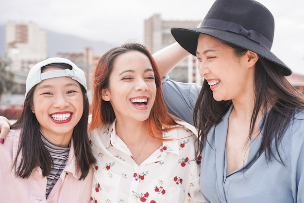 Asiatische freundinnen, die spaß im freien haben. glückliche trendige mädchen, die zusammen lachen Premium Fotos