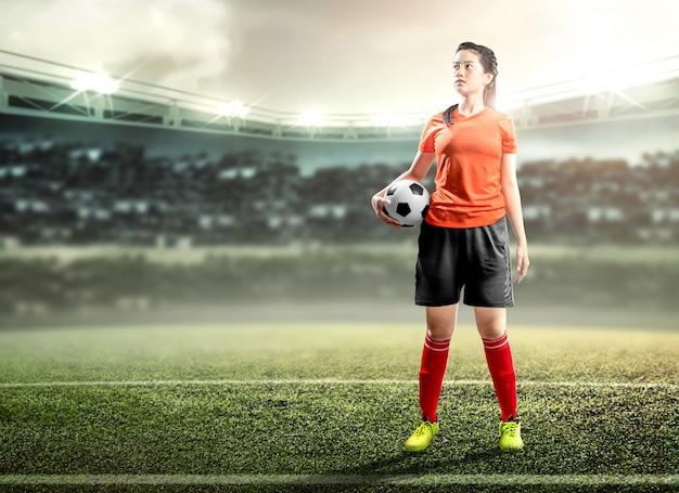 Asiatische fußballspielerfrau, die den ball auf dem fußballplatz hält Premium Fotos