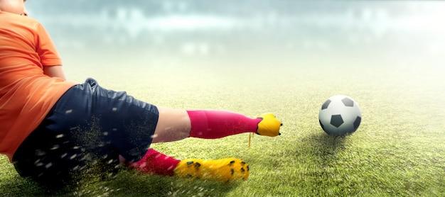 Asiatische fußballspielerfrau im orange trikot, das gerät die kugel schiebt Premium Fotos