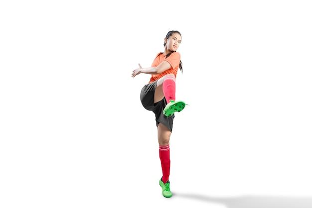 Asiatische fußballspielerfrau in der haltung des tretens der kugel Premium Fotos