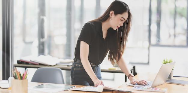 Asiatische geschäftsfrau, die an dem projekt mit laptop arbeitet Premium Fotos