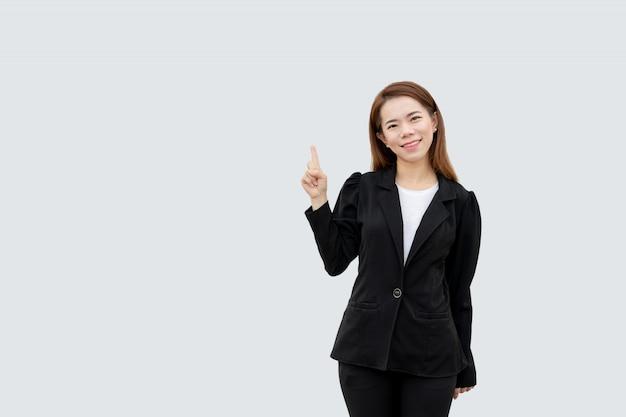 Asiatische geschäftsfrau, die finger zeigt, der mit langen haaren im schwarzen anzug lokalisiert auf weißer farbe präsentiert Premium Fotos
