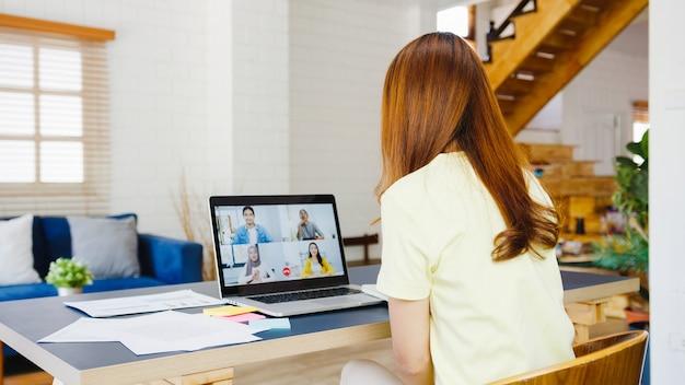 Asiatische geschäftsfrau, die laptop verwendet, spricht mit kollegen über plan in videoanrufbesprechung, während sie von zu hause im wohnzimmer arbeiten. selbstisolation, soziale distanzierung, quarantäne zur vorbeugung von koronaviren. Kostenlose Fotos
