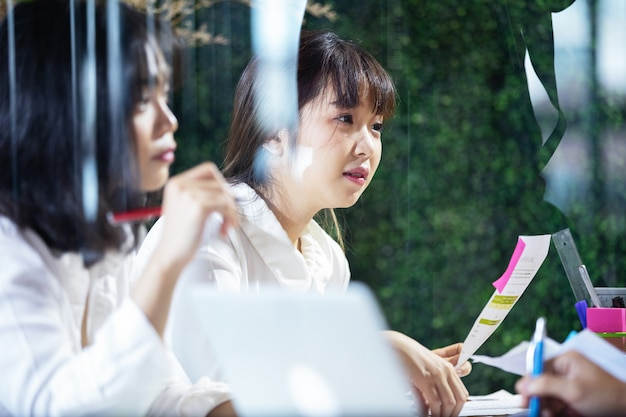 Asiatische geschäftsfrau, die seinem kollegen etwas erklärt Premium Fotos