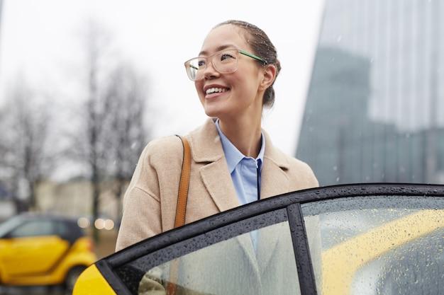 Asiatische geschäftsfrau, die taxi in der regnerischen straße nimmt Kostenlose Fotos