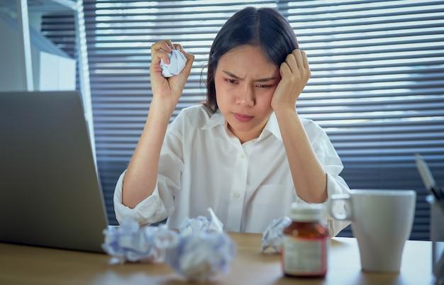 Asiatische geschäftsfrau, die unter starken kopfschmerzen oder migräne wegen der harten arbeit und des druckes leidet. Premium Fotos