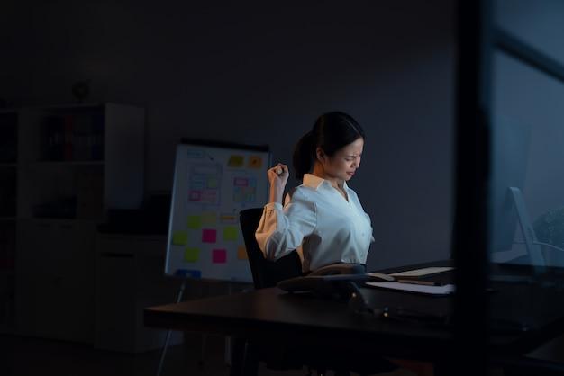 Asiatische geschäftsfrau hat nackenschmerzen, weil sie den computer benutzt und nachts lange arbeitet. Premium Fotos