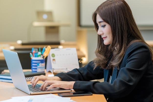 Asiatische geschäftsfrau im gesellschaftsanzug, der mit computerlaptop arbeitet Premium Fotos