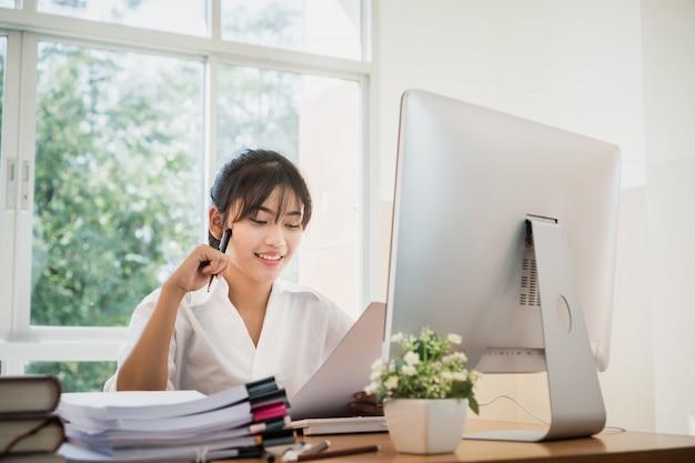 Asiatische geschäftsfraubürokontrolle, die für unfertigen stapel der dokumente dokumentenpapiere mit an beschäftigtem büro des computers arbeitet Premium Fotos