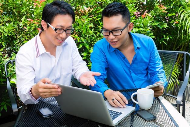 Asiatische geschäftsleute arbeiten im freien Premium Fotos