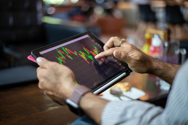 Asiatische geschäftsleute, die ein tablett zum arbeiten und überprüfen des aktien-trenddiagramms und der finanzanalyse im café verwenden Premium Fotos