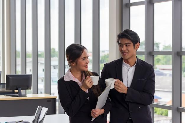 Asiatische geschäftsleute und frauen, die eine weiße kaffeetasse während des bruches im büro halten Premium Fotos