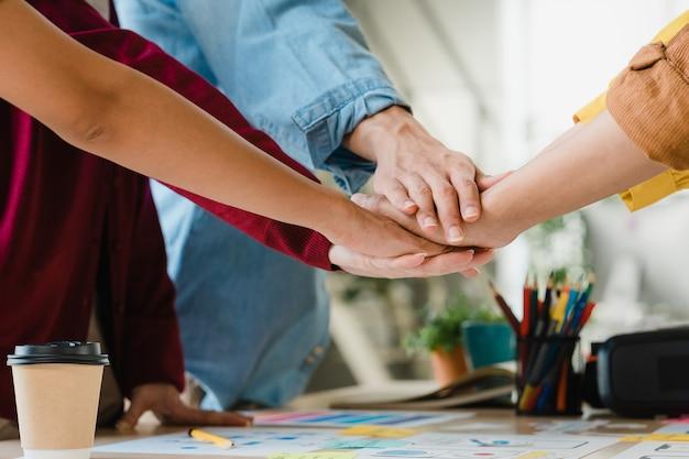 Asiatische geschäftsleute und geschäftsfrauen treffen sich beim brainstorming, um die hände für ein neues startup zu legen und die motivation zu stärken, in einem modernen kreativbüro zusammenzuarbeiten. teamwork-konzept für mitarbeiter. Kostenlose Fotos