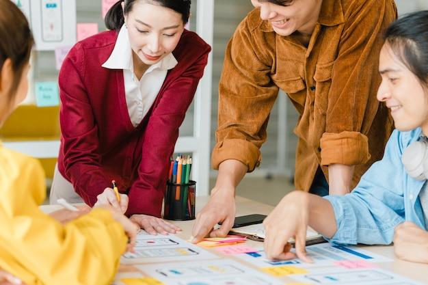 Asiatische geschäftsleute und geschäftsfrauen treffen sich mit brainstorming-ideen über kreative webdesign-planungsanwendungen und entwickeln ein vorlagenlayout für ein mobiltelefonprojekt, das in einem kleinen büro zusammenarbeitet. Kostenlose Fotos