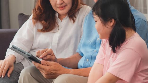 Asiatische großeltern und enkelin, die zu hause tablette verwendet. der ältere glückliche chinese, der großvater und die großmutter verbringen familienzeit mit dem jungen mädchen, das social media überprüft und liegen auf sofa im wohnzimmerkonzept Kostenlose Fotos