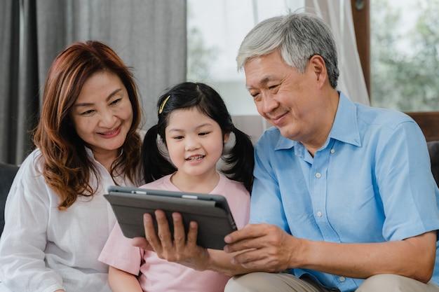 Asiatische großeltern und enkelin videoanruf zu hause. älterer chinese, großvater und großmutter glücklich mit dem mädchen, das den handyvideoanruf spricht mit dem vati und mutter zu hause liegt im wohnzimmer verwendet. Kostenlose Fotos