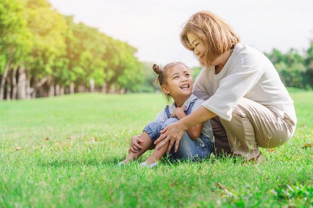 Asiatische großmutter und enkelkinder, die zusammen glückliche zeit im park haben Premium Fotos