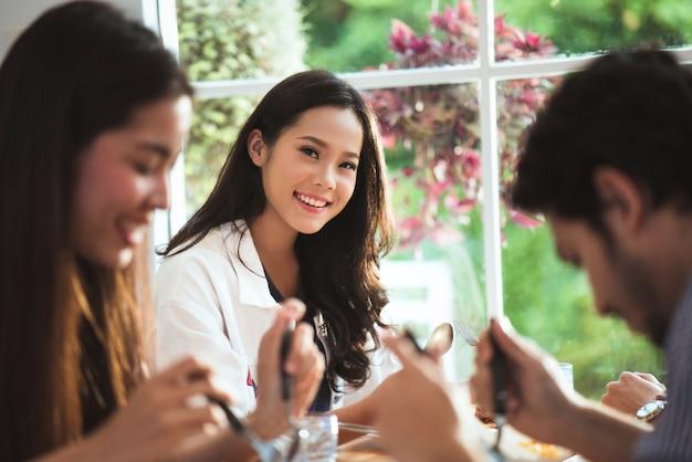 Asiatische gruppe, die restaurant isst, sie lächelte. Premium Fotos