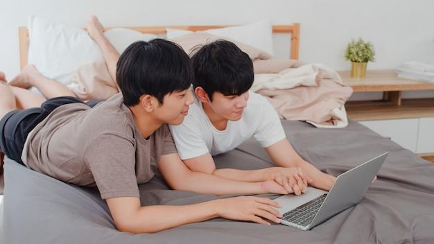 Asiatische homosexuelle lgbtq mannpaare unter verwendung des computerlaptops am modernen haus. das junge männliche glückliche asien-liebhaber entspannen sich rest zusammen, nachdem sie aufwachen und morgens den film aufpassen, der auf bett im schlafzimmer am haus liegt. Kostenlose Fotos