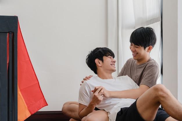 Asiatische homosexuelle paare, die zu hause auf dem boden liegen und umarmen. die jungen asiatischen lgbtq + männer, die glücklich küssen, entspannen sich rest verbringen zusammen romantische zeit im wohnzimmer mit regenbogenflagge am modernen haus morgens. Kostenlose Fotos