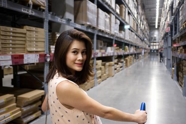 Asiatische hübsche frau mit dem lächelnden gesicht, das eine laufkatze drückt, sucht nach einigen einzelteilen im lager Premium Fotos