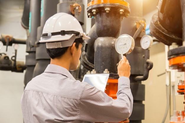 Asiatische ingenieurwartung, die kondensator-wasserdruckprüfer überprüft Premium Fotos