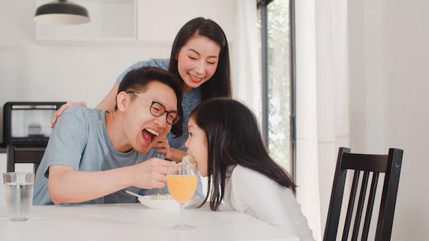 Asiatische japanische familie frühstückt zu hause. asiatischer glücklicher vati, mutter und tochter essen orangensaft des spaghettigetränks auf tabelle in der modernen küche am haus morgens. Kostenlose Fotos