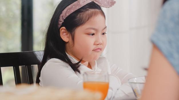 Asiatische japanische tochter mit essen gelangweilt. lebensstil scherzt traurige abneigung gegen umgekippte frühstücksmahlzeit des lebensmittels in der modernen küche am haus morgens. Kostenlose Fotos