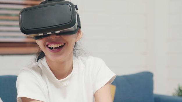 Asiatische jugendlichfrau, die den simulator der virtuellen realität der gläser spielt videospiele im wohnzimmer verwendet Kostenlose Fotos