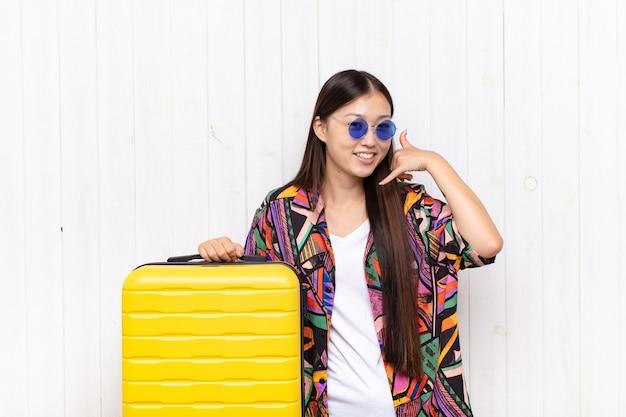 Asiatische junge frau, die fröhlich lächelt und auf kamera zeigt, während sie einen anruf sie später geste machen, am telefon sprechen Premium Fotos