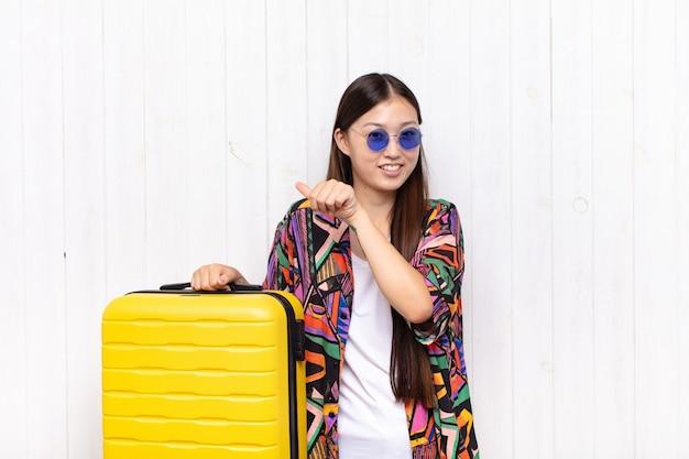 Asiatische junge frau, die fröhlich lächelt und beiläufig auf die seite zeigt Premium Fotos