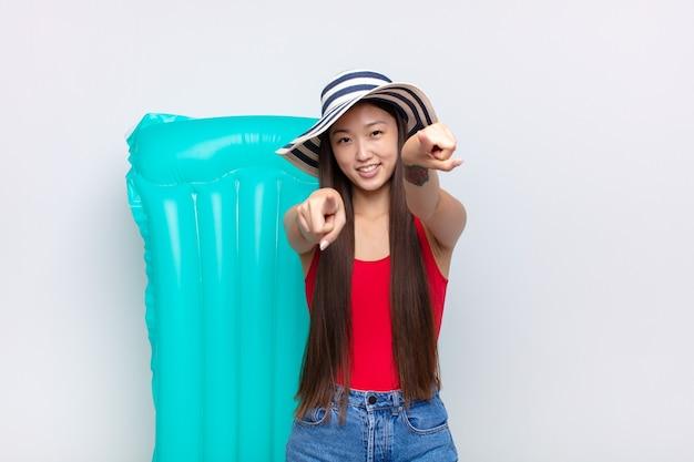 Asiatische junge frau, die glücklich und zuversichtlich fühlt, mit beiden händen nach vorne zeigt und lacht, sie wählt. sommerkonzept Premium Fotos