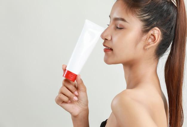 Asiatische junge frau, die rohr der feuchtigkeitscreme hält Kostenlose Fotos