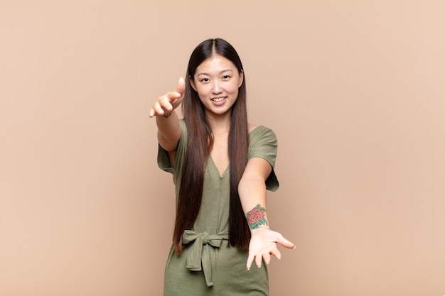 Asiatische junge frau lächelt fröhlich und gibt eine warme, freundliche Premium Fotos
