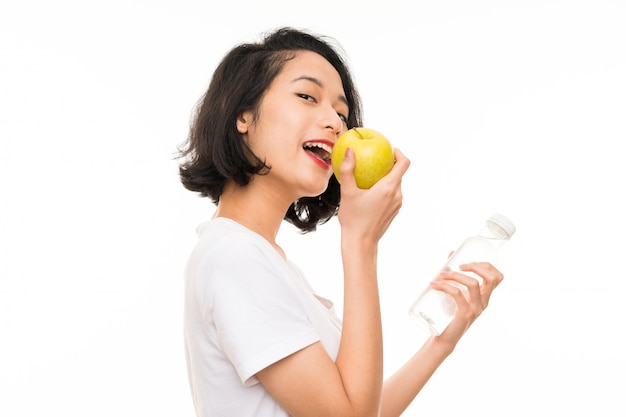 Asiatische junge frau mit einem apfel und einer flasche wasser Premium Fotos