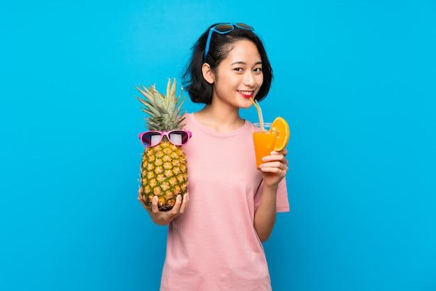 Asiatische junge frau über der lokalisierten blauen wand, die eine ananas mit sonnenbrille hält Premium Fotos