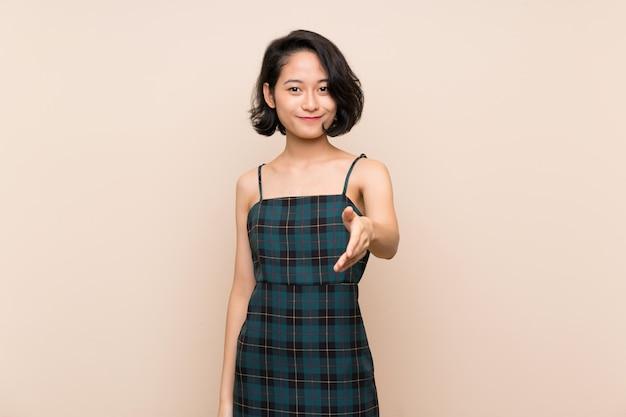 Asiatische junge frau über der lokalisierten gelben wand, die hände für das schließen viel rüttelt Premium Fotos