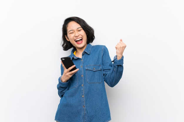 Asiatische junge frau über lokalisierter weißer wand mit telefon in siegposition Premium Fotos