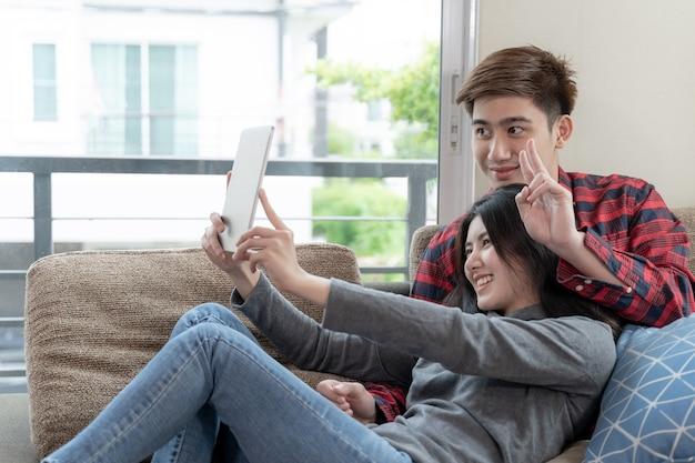 Asiatische junge frau und gutaussehender mann, die auf couch unter verwendung des geräts sitzt Kostenlose Fotos
