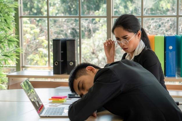 Asiatische junge frauen fühlen sich gelangweilt, wenn sie ihre schlafenden kollegen, geschäftskonzept sieht Premium Fotos