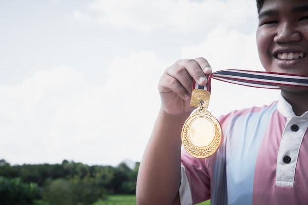 Asiatische junge gewinnerhand hob medaillen preise des wettbewerbskonzeptes an Premium Fotos