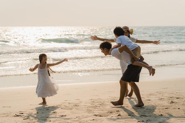 Asiatische junge glückliche familie genießen abends urlaub am strand. vater, mutter und kind entspannen sich beim spielen in der nähe des meeres bei sonnenuntergang während des reiseurlaubs. lifestyle reise urlaub urlaub sommer konzept. Kostenlose Fotos