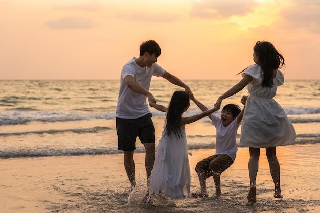 Asiatische junge glückliche familie genießen abends urlaub am strand. vater, mutter und kind entspannen sich beim spielen zusammen in der nähe des meeres, wenn silhouette sonnenuntergang. lifestyle reise urlaub urlaub sommer konzept. Kostenlose Fotos