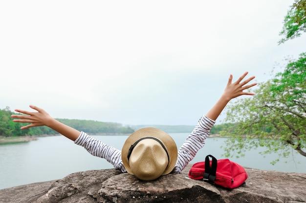 Asiatische junge mädchen mit dem hellen rucksack, der in der natur während der ferien genießt. Premium Fotos