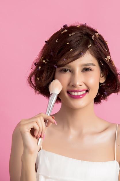 Asiatische junge schönheit des kurzen haares, die kosmetischen puderpinsel aufträgt Kostenlose Fotos