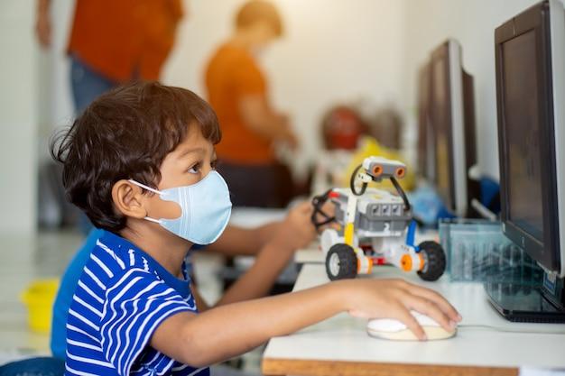 Asiatische jungen tragen gesichtsmasken, um das coronavirus 2019 (covid-19) in schulen zu verhindern. Premium Fotos