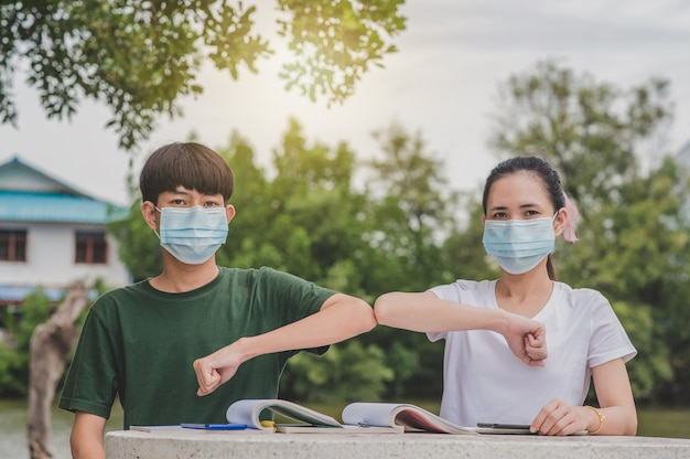 Asiatische jungen und mädchen zurück in die schule eine tragende gesichtsmaske und händeschütteln halten new normal keine rührende soziale distanzierung Premium Fotos