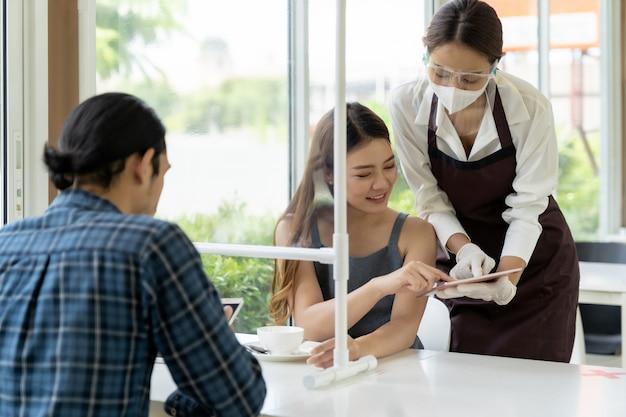 Asiatische kellnerin schuhmenü mit tablette. Premium Fotos