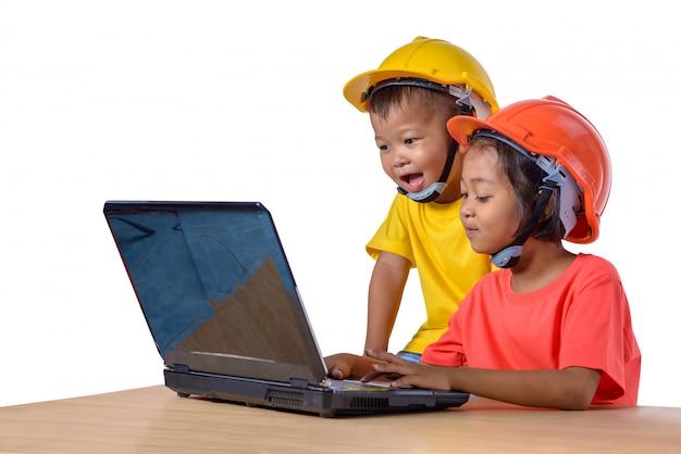 Asiatische kinder, die den schutzhelm tragen und den hobel lokalisiert auf weiß denken Premium Fotos